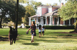 Children run and frolic on the lawn at Poche Plantation